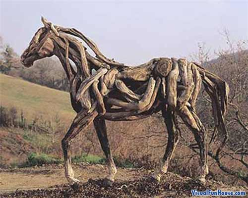 Woodedn Horse sculpture in filed