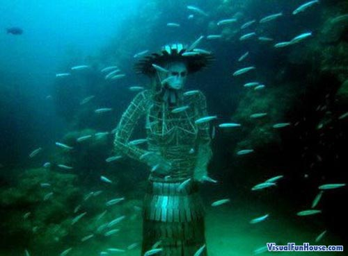 Underwater lady statue surrounded by fish