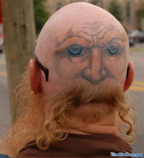 A tattooed rear creates a two faced tattoo effect on this mans head.